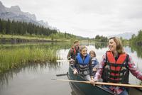 Family sitting in canoe in still lake