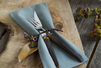Tied napkin and silverware on wooden cutting board