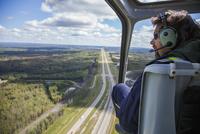 Pilot in helicopter flying over landscape 11096004877| 写真素材・ストックフォト・画像・イラスト素材|アマナイメージズ