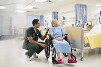 Male nurse talking to woman in hospital wheelchair 11096006191| 写真素材・ストックフォト・画像・イラスト素材|アマナイメージズ