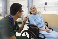 Male nurse talking to woman in hospital wheelchair