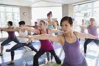 Women practicing warrior 2 pose in yoga class