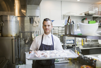 Portrait chef holding tray of raw chicken wings
