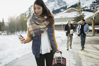 Woman pulling suitcase on sidewalk below mountains 11096006916  写真素材・ストックフォト・画像・イラスト素材 アマナイメージズ