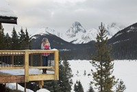 Woman looking at mountain view from lodge deck