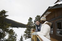 Couple talking on snowy lodge deck