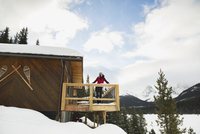 Woman on snowy lodge deck below mountains