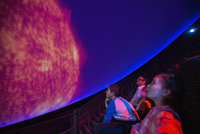 Students watching planet at planetarium show