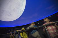 Curious students watching moon in planetarium show