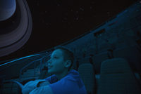 Curious boy enjoying planetarium show