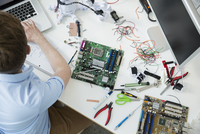 Engineer assembling circuit boards and working at laptop