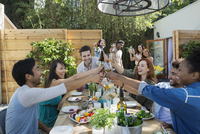 Friends toasting wine glasses at patio table