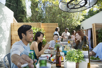 Friends eating and drinking at patio table