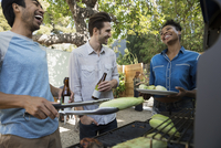 Smiling friends drinking beer and barbecuing corn cobs
