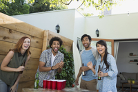 Laughing friends playing beer pong on patio