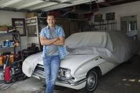 Portrait man leaning on covered vintage car garage 11096009907| 写真素材・ストックフォト・画像・イラスト素材|アマナイメージズ