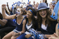 Enthusiastic fans in blue cheering bleachers sports event