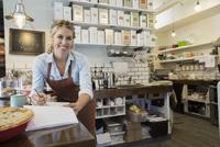 Portrait confident tea shop owner doing paperwork counter