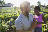 Father holding daughter in sunny garden
