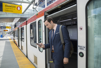 Businessman disembarking train texting with cell phone