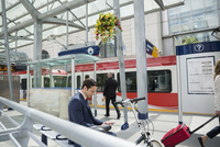 Businessman texting with cell phone at trains station 11096012453| 写真素材・ストックフォト・画像・イラスト素材|アマナイメージズ