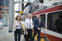 Business people walking along train station platform 11096012456| 写真素材・ストックフォト・画像・イラスト素材|アマナイメージズ