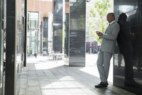 Businessman texting with cell phone on urban sidewalk