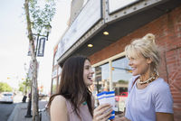 Enthusiastic mother and daughter holding tickets outside theater
