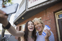 Mother and daughter taking selfie tickets outside theater
