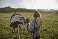 Pensive female rancher with horse sunny remote field 11096012836  写真素材・ストックフォト・画像・イラスト素材 アマナイメージズ