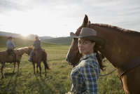 Portrait smiling female rancher with horse in field