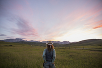 Female rancher watching dramatic sunset sky over field