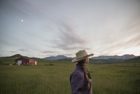 Pensive female rancher watching dramatic sunset sky field