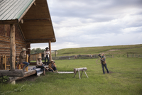 Female ranchers practicing roping outside cabin