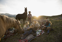 Female ranchers camping in remote field playing guitar