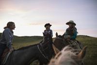 Female ranchers on horseback talking under sunset sky