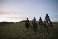 Female ranchers horseback riding in field at sunset