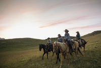 Female ranchers horseback riding under sunset sky