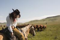 Female rancher horseback adjusting saddlebag herding cattle