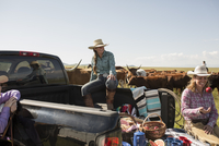 Female ranchers with cattle enjoying truck bed picnic