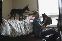 Man holding cat on bedroom floor 11096013787| 写真素材・ストックフォト・画像・イラスト素材|アマナイメージズ