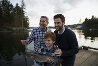 Multi-generation men caught fish lake dock sunset