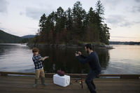 Father photographing son caught fish lake at sunset