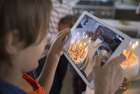 Boy photographing birthday cake with candles