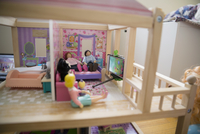 Dolls watching TV on cell phone in dollhouse