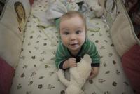 Portrait cute baby boy laying crib stuffed animal