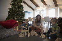 Mother and sons playing wood blocks Christmas tree