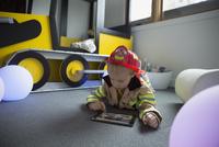 Boy fireman costume using digital tablet floor