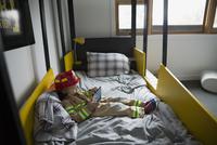 Boy fireman costume using digital tablet bed