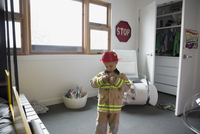 Boy putting on fireman costume in bedroom